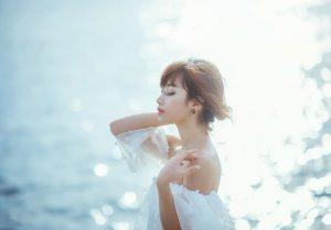 水辺で風を感じる女性