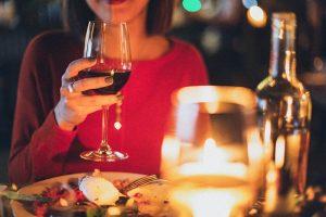 ディナーでワインを飲む女性