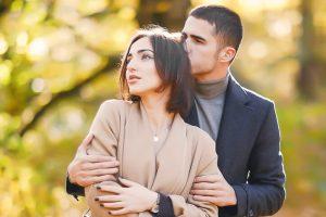 女性が遠くを見つめ抱きかかえる男性
