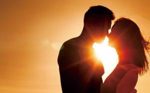 夕日をバックにキスをする男女