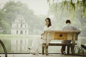 湖の公園のベンチでつまらなそうにしている女性