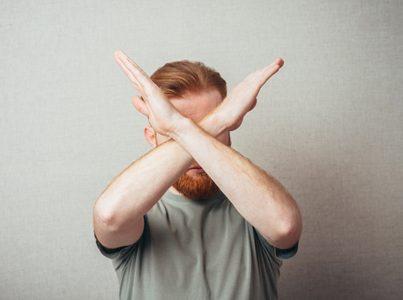 両腕でバツ印を出す 男性