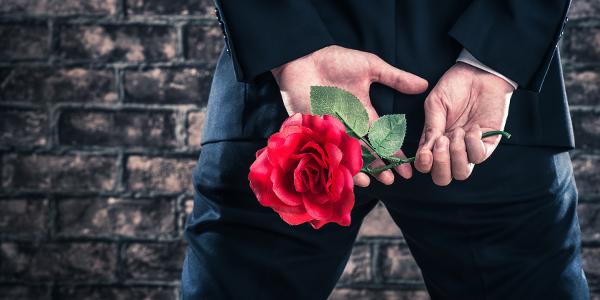 一輪のバラを隠し持つ男性