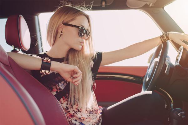 かっこよく車を運転する金髪女性