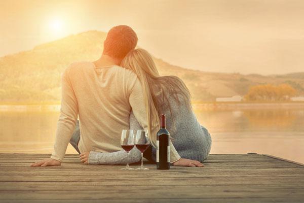 湖でお酒を飲みながらいちゃつく男女