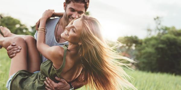野原で女性を抱きかかえる男性