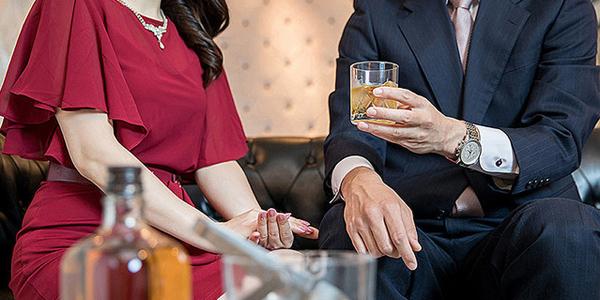 酒を飲む男性と接待する女性