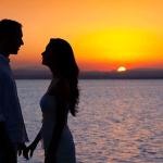 夕焼けの浜辺で向かい合うカップル